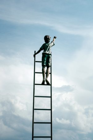 A child standing at the stop of a stair and reaching for the sky